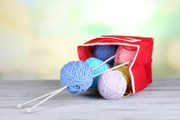 素朴なクラフトバッグ、om木製テーブル、明るい表面の羊毛の糸のボール