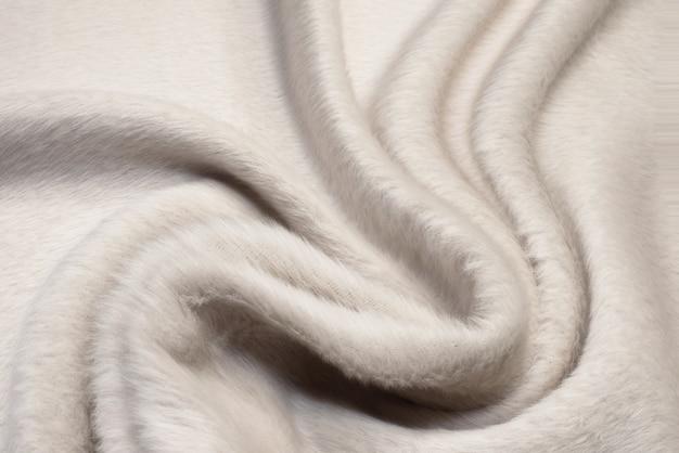 柔らかい折り目でウールベージュの毛皮のような生地