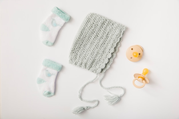 Woolen headwear; socks and pacifiers on white backdrop
