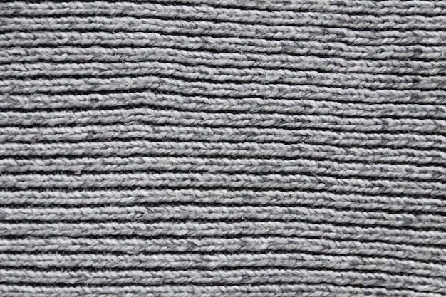 グレーのテキスタイルのウールニットの表面をクローズアップ。自然なテキスタイルの背景。厚手の編みパターン。