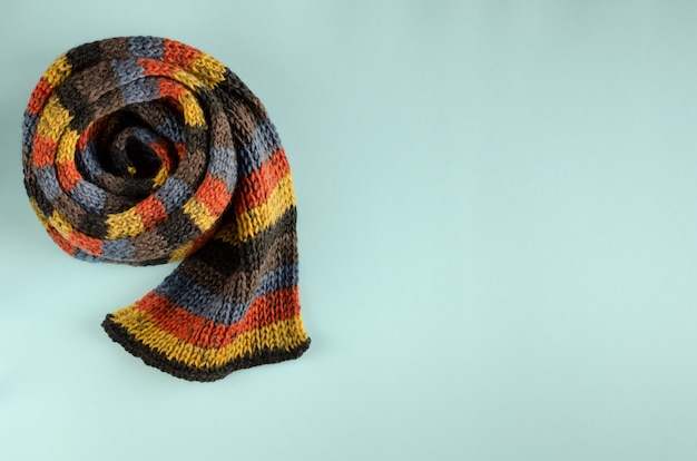 Woolen scarf composition on blue background. flat lay.