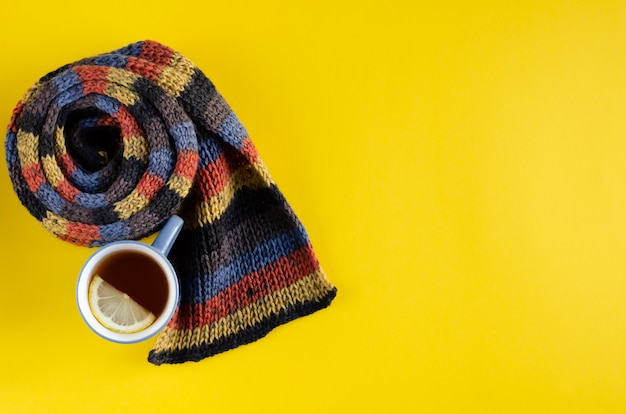 Woolen scarf with tea cup and lemon slice composition on yellow background.
