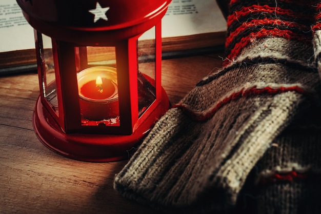 Woolen sweater and a lantern with a candle. cozy autumn and winter concept