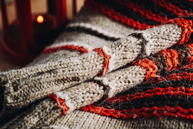 A woolen sweater and lantern with candle.