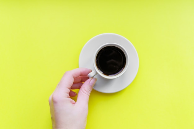 Wooman's hand holding cup of coffee- top view of minimal flat lay on yellow background.
