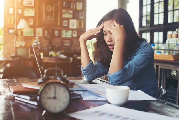 Worのためのストレスの多い彼女のラップトップとカフェに座って若い女性、