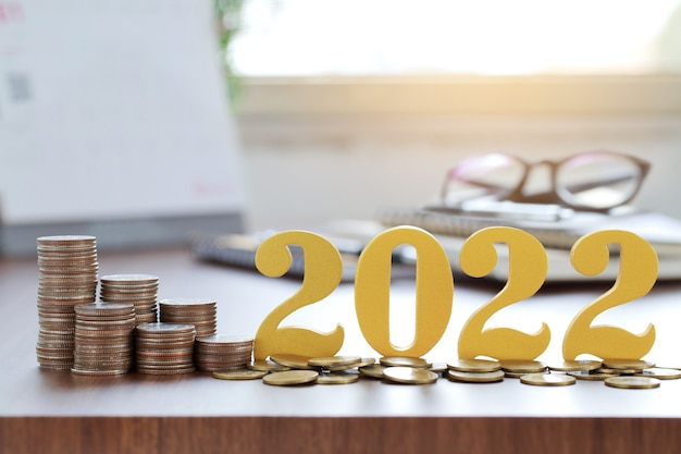 Word 2022 put on coins with coins stack on desk .savings new year concept.
