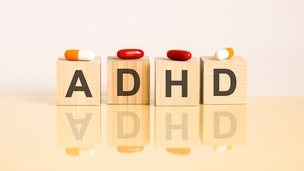 Word adhd is made of wooden cubes on a yellow background with pills. medical concept of treatment, prevention and side effects. adhd - short for attention deficit hyperactivity syndrome