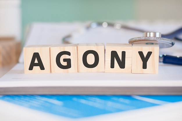 The word agony is written on wooden cubes near a stethoscope on a paper background.