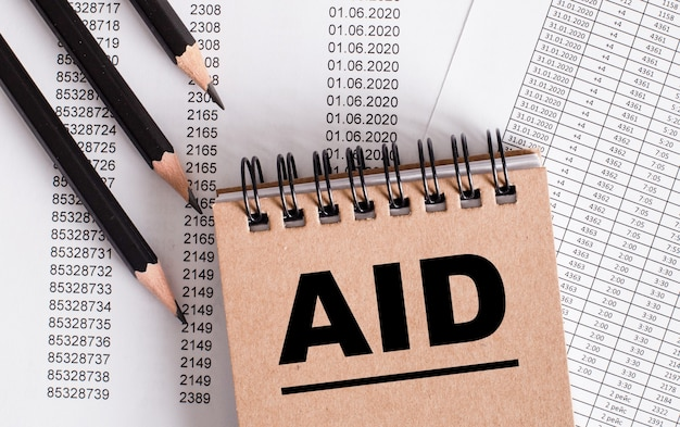 The word aid is written on the brown notebook.