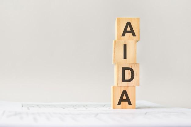 나무 빌딩 블록이 있는 word aida, 밝은 회색 배경. 배경, 비즈니스 개념에 숫자가 있는 문서. 오른쪽에 텍스트를 위한 공간입니다. 전면보기.