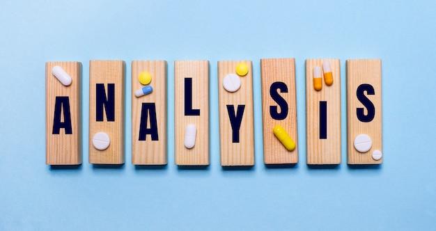 The word analysis is written on wooden blocks on a light blue table near the pills