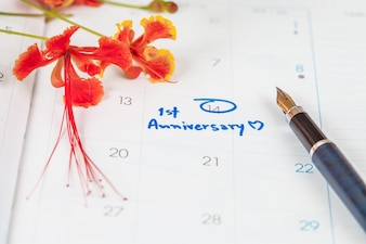 Word anniversary celebration plan on calendar with flower and pen