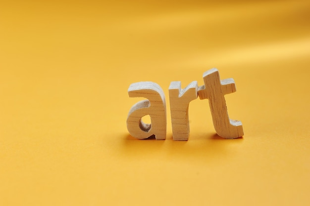 Word art carved from wood stand on yellow backdrop for your desing, art text concept.