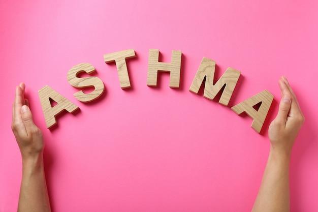 Слово астма из деревянных букв и женских рук на розовом фоне