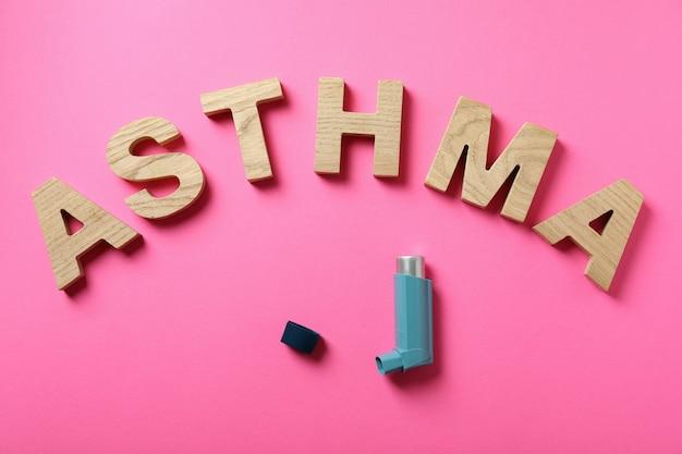 Слово астма из деревянных букв и ингалятор на розовом фоне