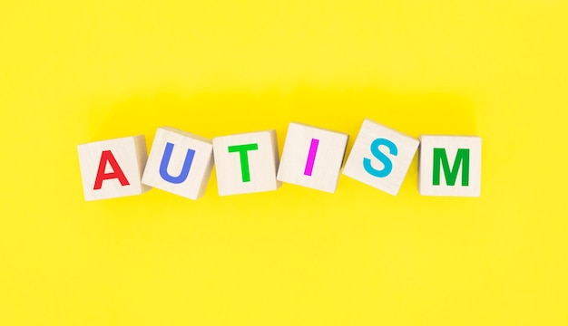 黄色の背景に木製の立方体の単語自閉症。