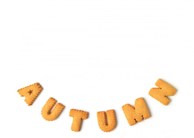 The word autumn spelled with alphabet shaped biscuits on white,