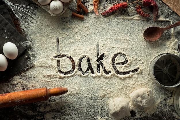 Слово выпекать на кулинарии фоне с мукой на столе