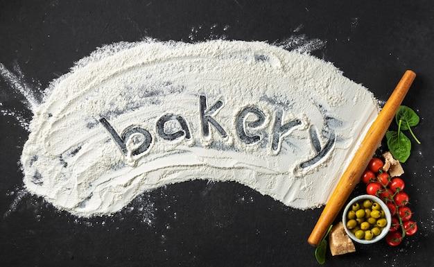 Пекарня слово написано на муке со скалкой и ингредиентами для приготовления итальянской кухни, вид сверху. абстрактный фон выпечки