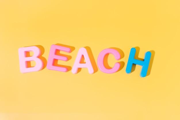 Слово пляж в цветах на желтом фоне копией пространства летом концепции
