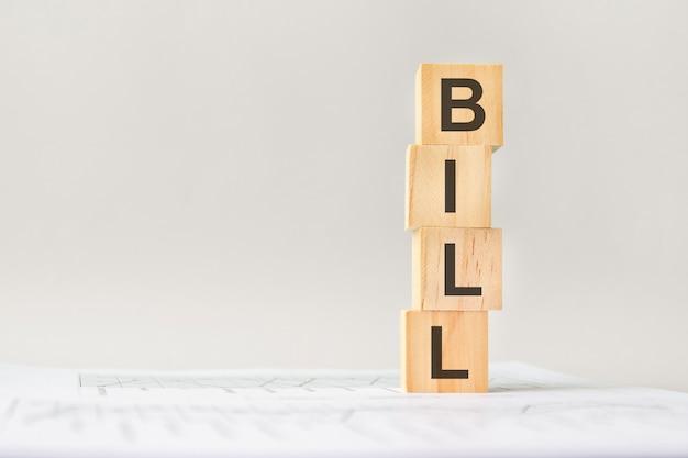 Билл слова с деревянными строительными блоками, светло-серым фоном. документ с числами на фоне, бизнес-концепция. место для текста слева. передний план.