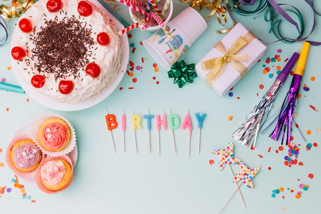 Word birthday candles with party accessories and cake on blue backdrop