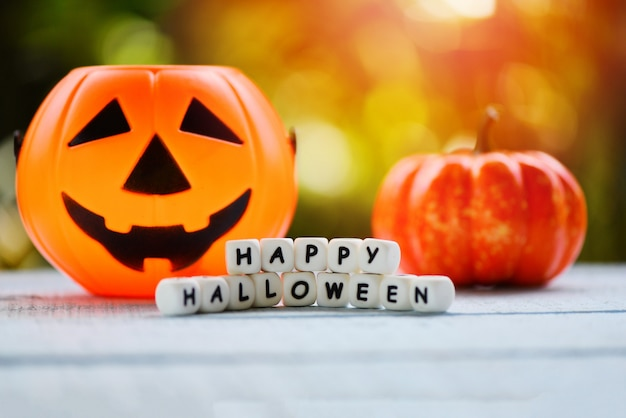 Word blocks happy halloween with decorations and pumpkin jack o lantern funny spooky