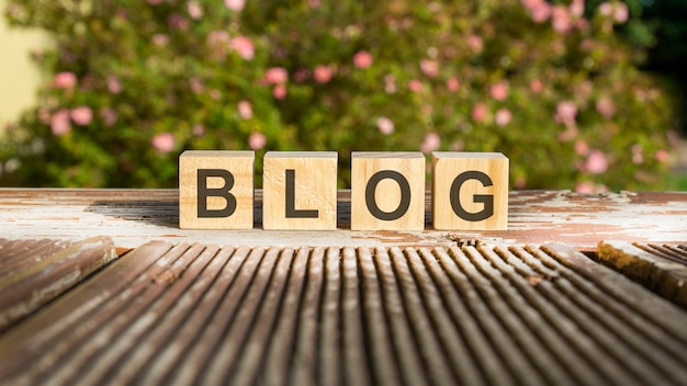 The word blog is written on wooden cubes. the blocks are placed on an old wooden board illuminated by the sun. in the background is a brightly blooming shrub