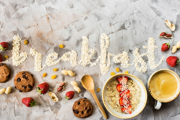 The word breakfast is written on a gray background of oatmeal