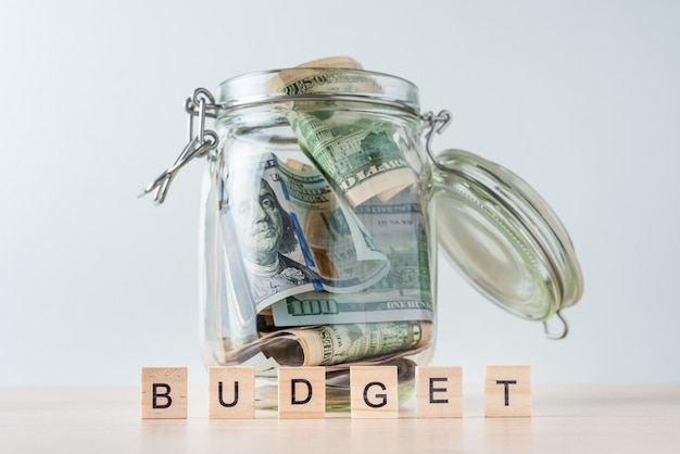 Word budget and dollar bills in glass jar