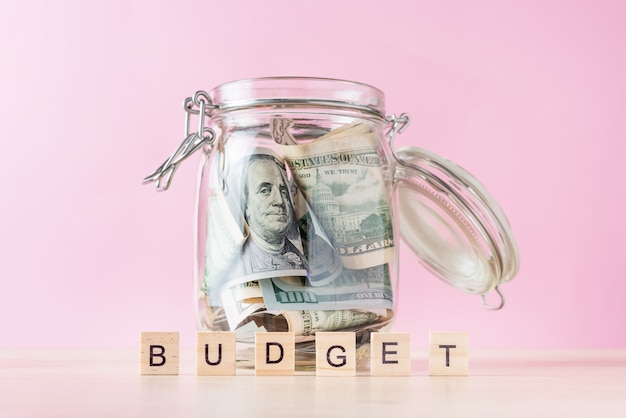 Word budget and dollar bills in glass jar