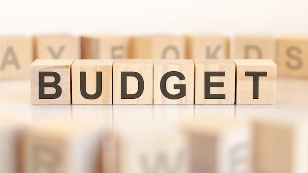 Бюджет слова написан на деревянных кубиках, стоящих в ряд. вокруг блоков с буквами на светлом фоне. может использоваться для бизнес-концепций и финансовых концепций. выборочный фокус.