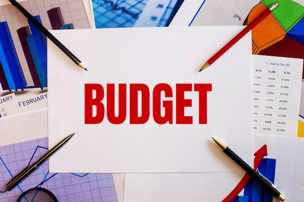 The word budget is written on a white wall near colored graphs, pens and pencils. business concept