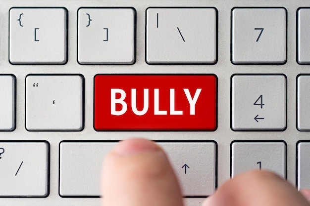 The word bullying on the computer's gray keyboard. the concept of harassment intimidation and humiliation in the network.