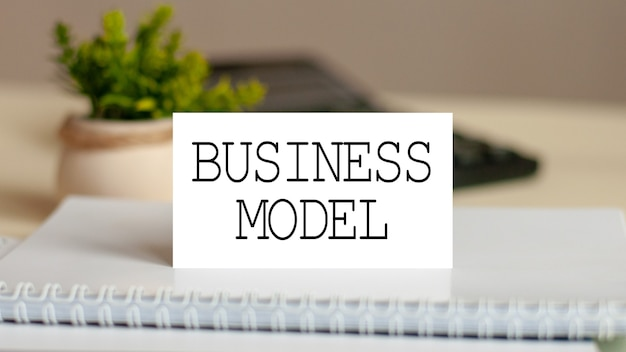 The word business model is written on the white card. card on the background of noteboook bills and a calculator. business concept Premium Photo