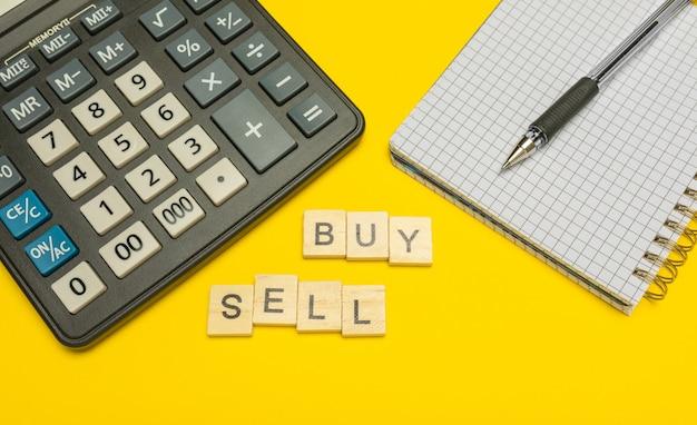 ペンとノートを備えた黄色のモダンな電卓に木製の文字で作られた単語の売買。