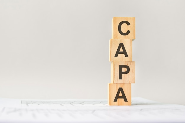 Word capa with wood building blocks, light gray background. document with numbers on background, business concept. space for text in left. front view.