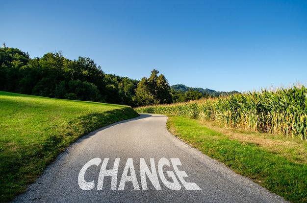 道路に白い色で描かれた「変化」という言葉、変化への道のコンセプト