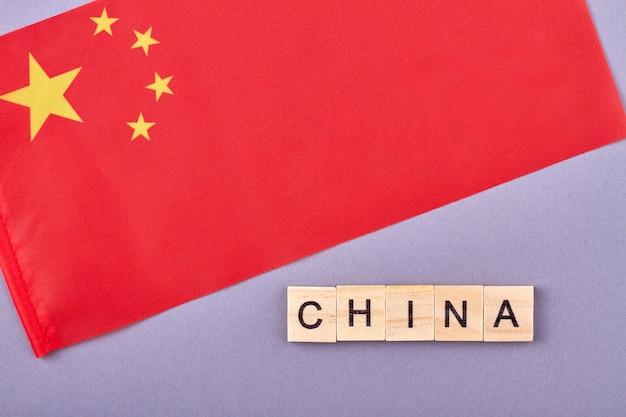 Слово китай из деревянных букв. красный флаг страны с желтыми звездами. изолированные на фиолетовом фоне.