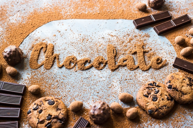 The word chocolate is laid out of cocoa on a gray background among cocoa