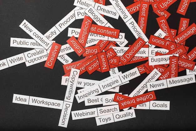 Word cloud of business themes cut out of red and white paper on a gray background