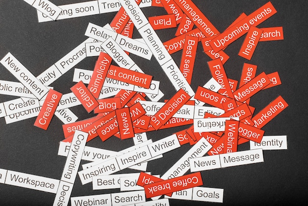 Word cloud of business themes cut out of red and white paper on a gray surface
