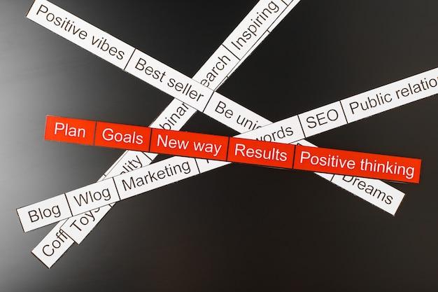 Облако слов бизнес-тем вырезано из красной и белой бумаги на черном фоне.