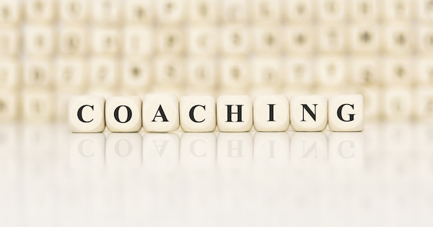 Word coaching written on wood block. business concept.