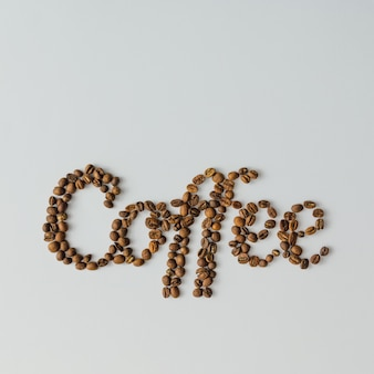 Word coffee made of coffee beans on bright surface with copy space