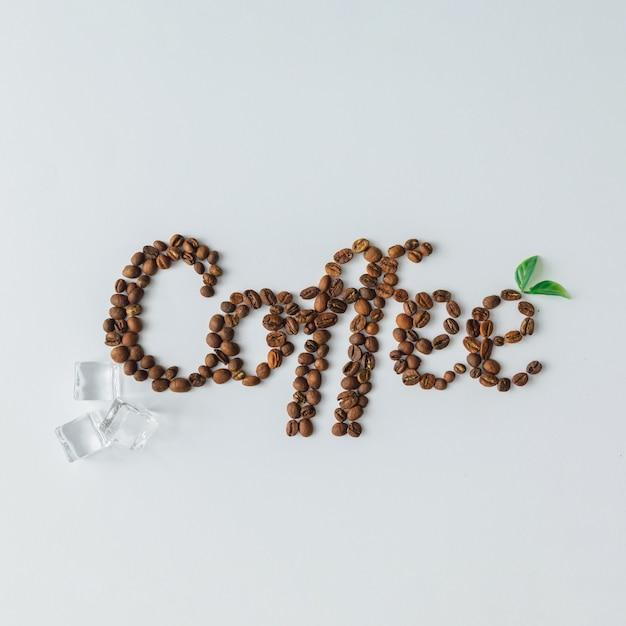 Слово кофе из кубиков льда и кофейных зерен на яркой поверхности