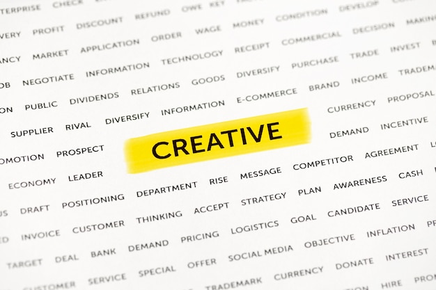 The word creative is highlighted with a marker on paper