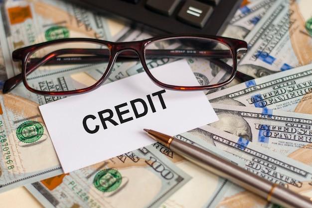 단어 신용은 배경, 비즈니스 및 금융의 개념에 지폐, 안경, 펜 및 계산기에 누워 흰색 카드에 기록됩니다