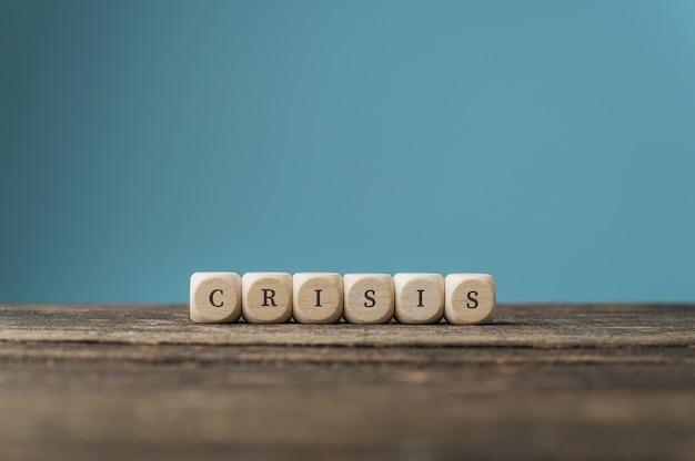 Слово кризис написано на деревянных кубиках, поставленных на стол